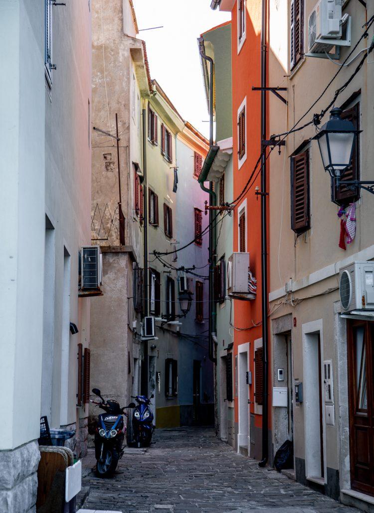 Vibrant colored buildings along a cobblestone street in Piran