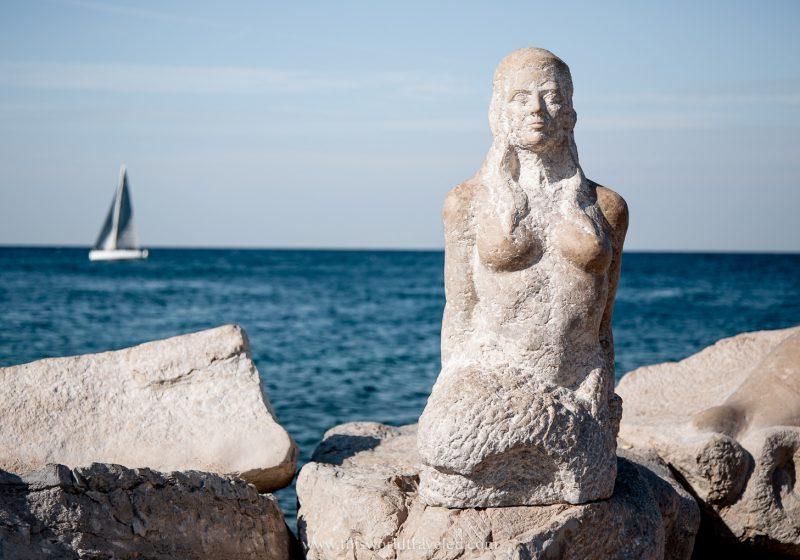A mermaid statue perched on the rocks linen the Adriatic Sea in Piran, Slovenia