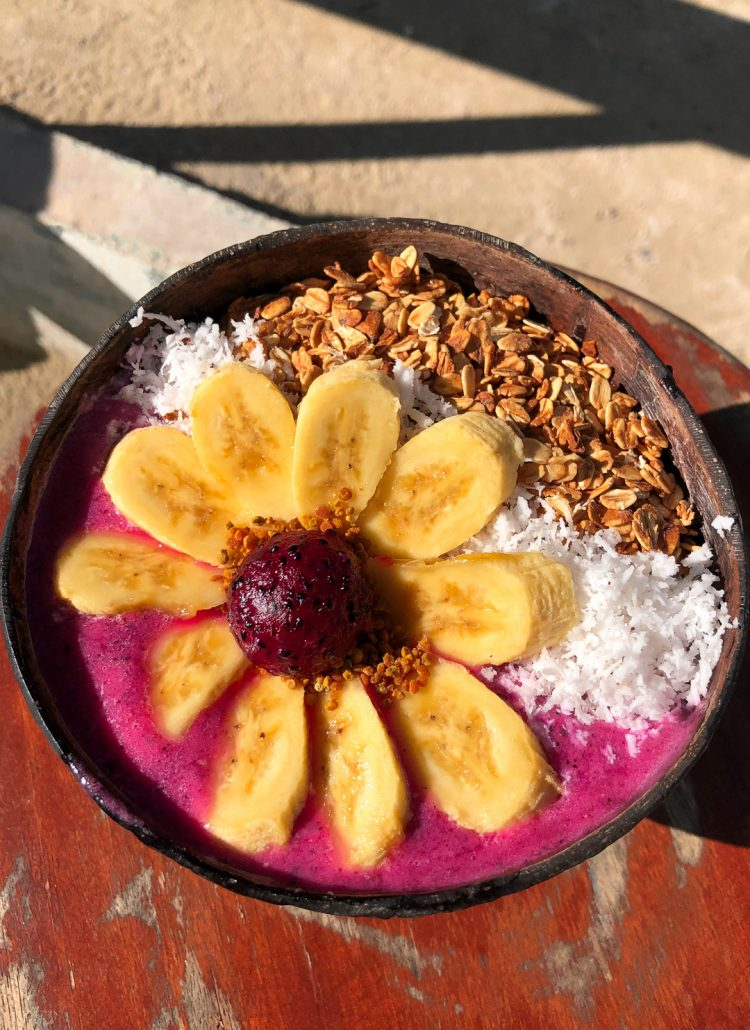 A pink colored smoothie bowl topped with coconut, granola and bananas