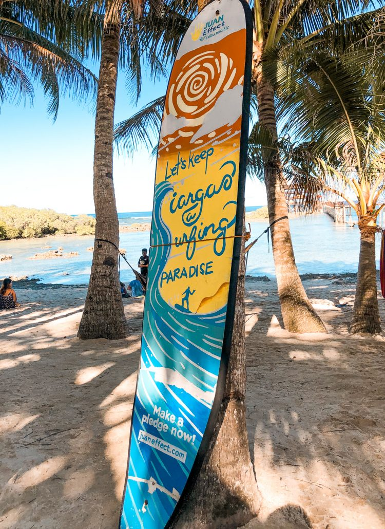 A surfboard leaning against a tree with a painting and writing