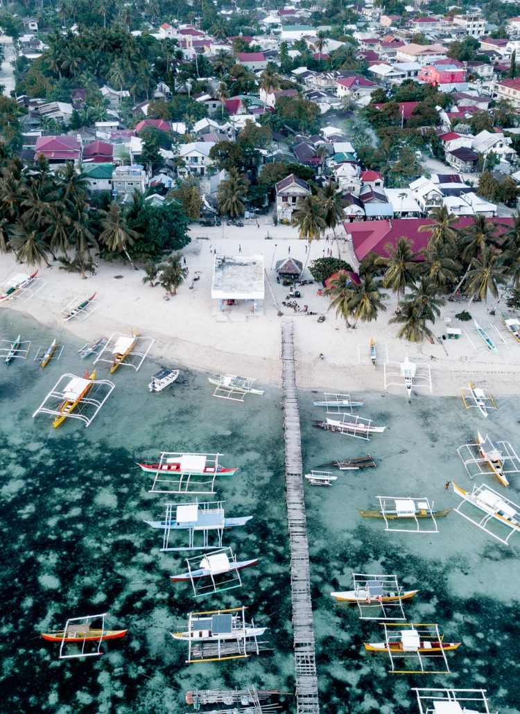 The small Dapa harbor in Siargao lined with traditional Philippine boats and surrounded by palm trees and houses