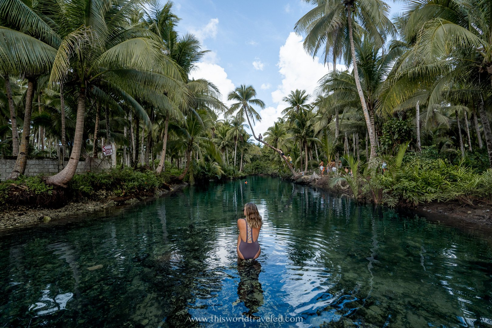 Girl in a bathing suit sitting in a river in the Philippines surrounded by coconut palm trees