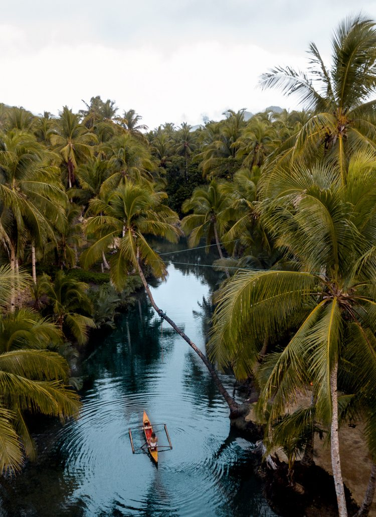 Girl in a traditional Philippine fishing boat in the Maasin River surrounded by palm trees in Siargao