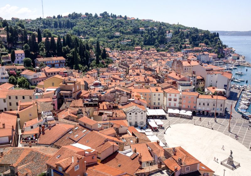 A large square located in the Old Town of Piran with views of the mountains and trees
