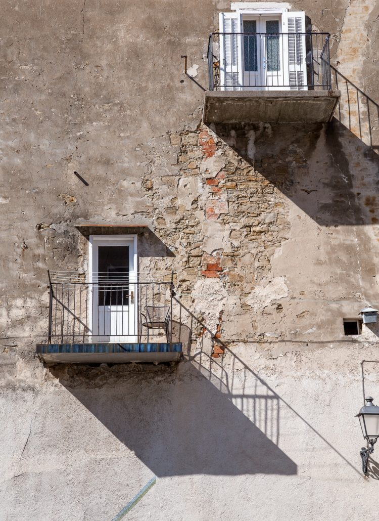 Small doors with a balcony and a concrete wall with bricks in Piran, Slovenia
