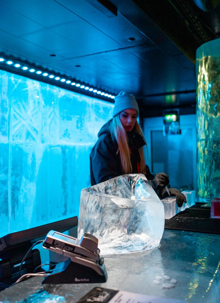 A girl behind an ice bar serving cocktails