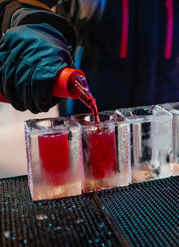 A red drink being poured into ice glasses