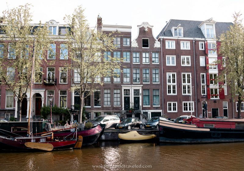 The brown and red colored row houses located along the canals in Amsterdam