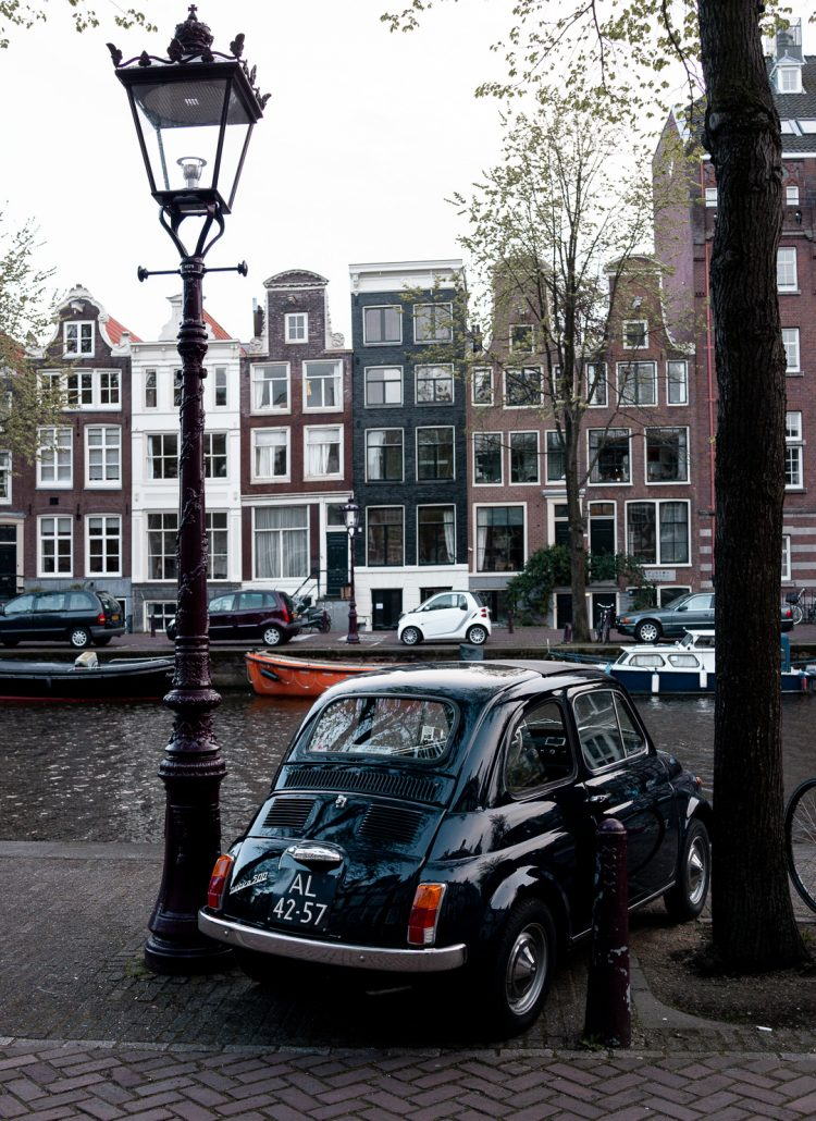 A small black car parked along the canals with gingerbread houses in Amsterdam