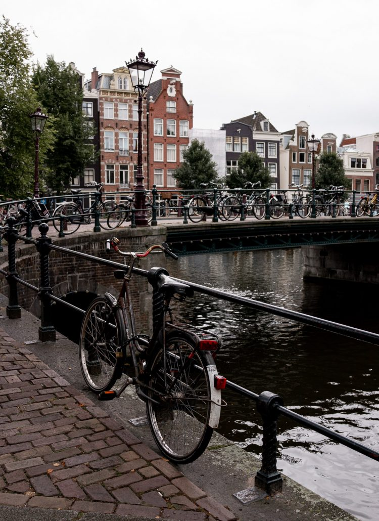 Bikes parked along the canals in Amsterdam with gingerbread houses