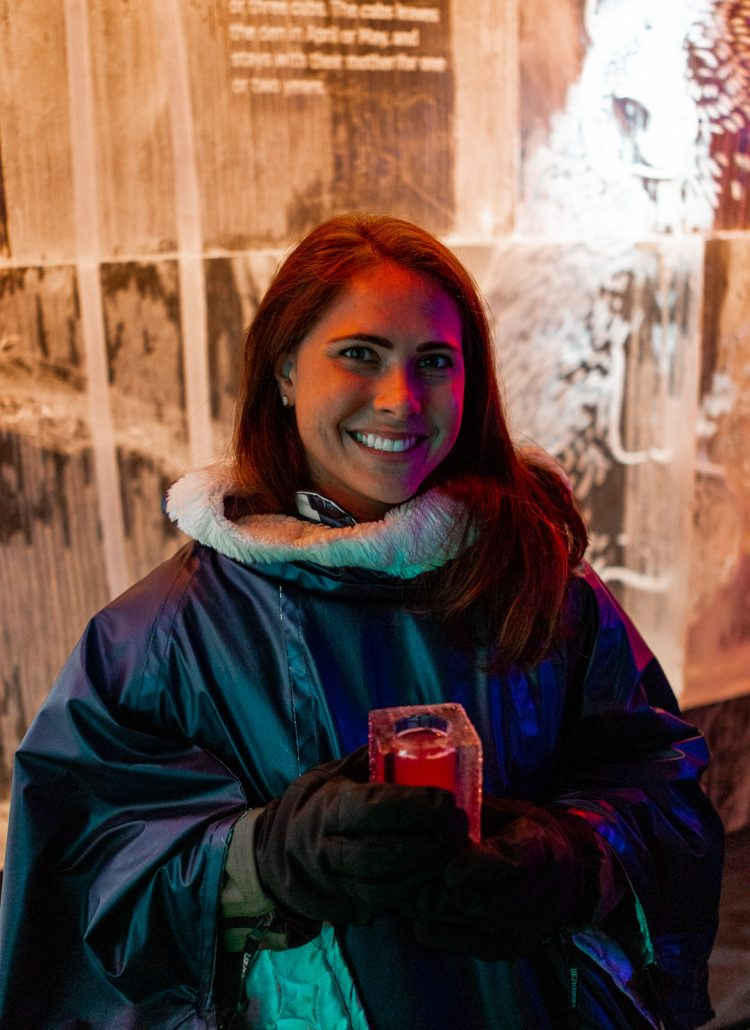 A girl with brown hair wearing a cape inside an icebar in Stockholm, Sweden