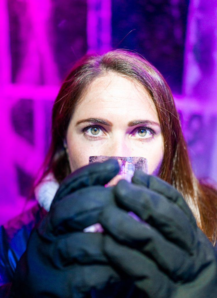 A girl with brown hair wearing gloves and drinking from a glass made of ice at the ICEBAR in Stockholm