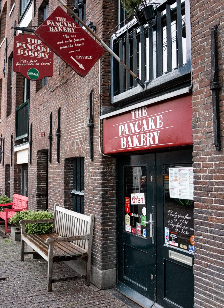 The outside of The Pancake Bakery in Amsterdam with a red sign and red flags