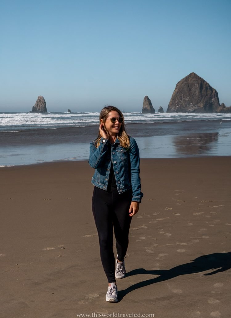 A girl with a jean jacket walking on the beach with a large rock formation