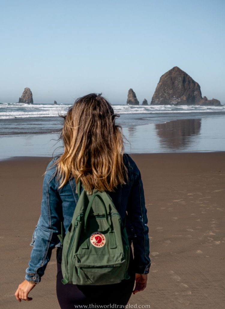 A girl with a green backpack walking on the beach in Oregon with a large rock formation coming out of the ocean