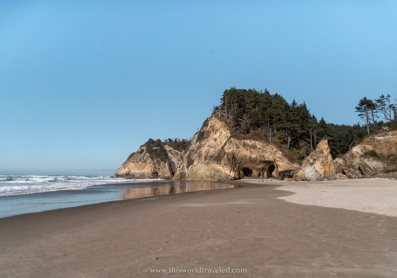 The large sandstone rock formations lining the beach at Hug Point in Oregon