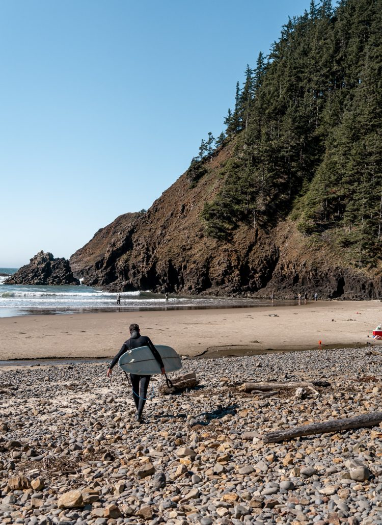 A man carrying a surfboard down to the ocean at Indian Beach in Ecola State Park