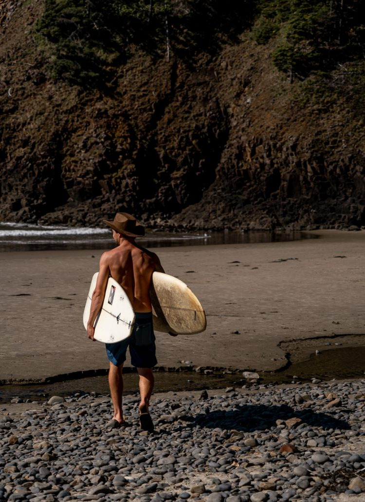 A man carrying two surfboards down to the ocean at Indian Beach in Ecola State Park