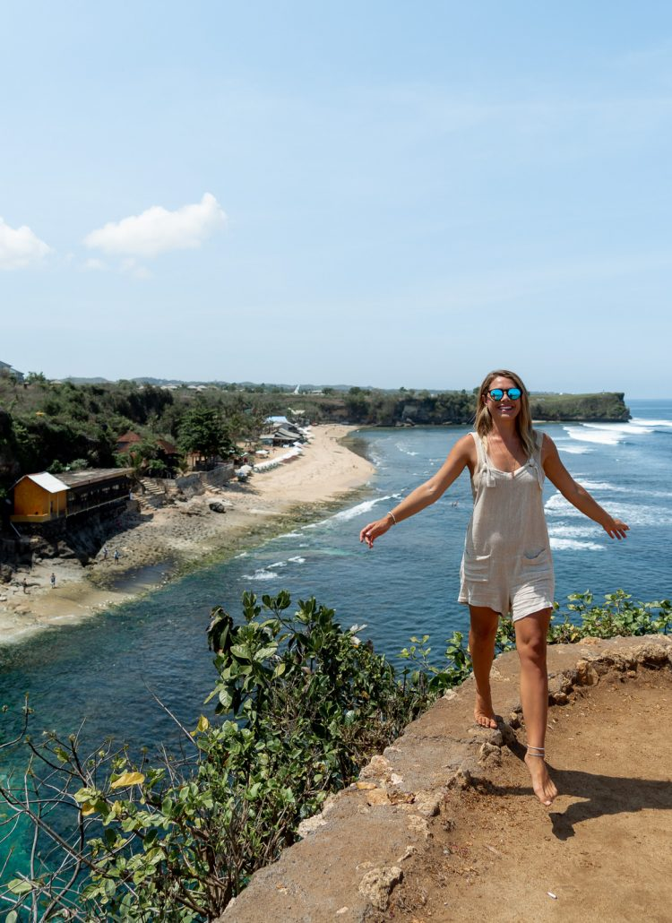 Girl standing on the side of a cliff overlooking Balagan Beach in Uluwatu, Bali