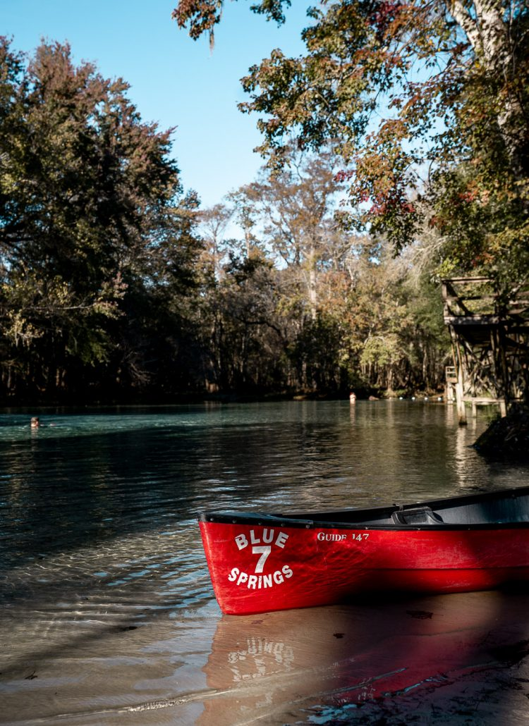 A red canoe at the edge of the Gilchrist Blue Springs surrounded by crystal clear water and cypress trees