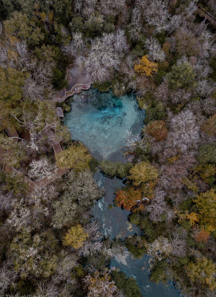 Drone shot of the blue hole with turquoise water surrounded by orange, green and yellow trees