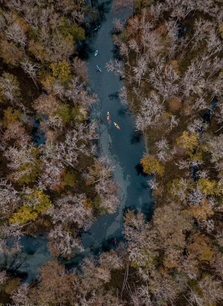 Drone shot of kayaks floating down a river with blue water