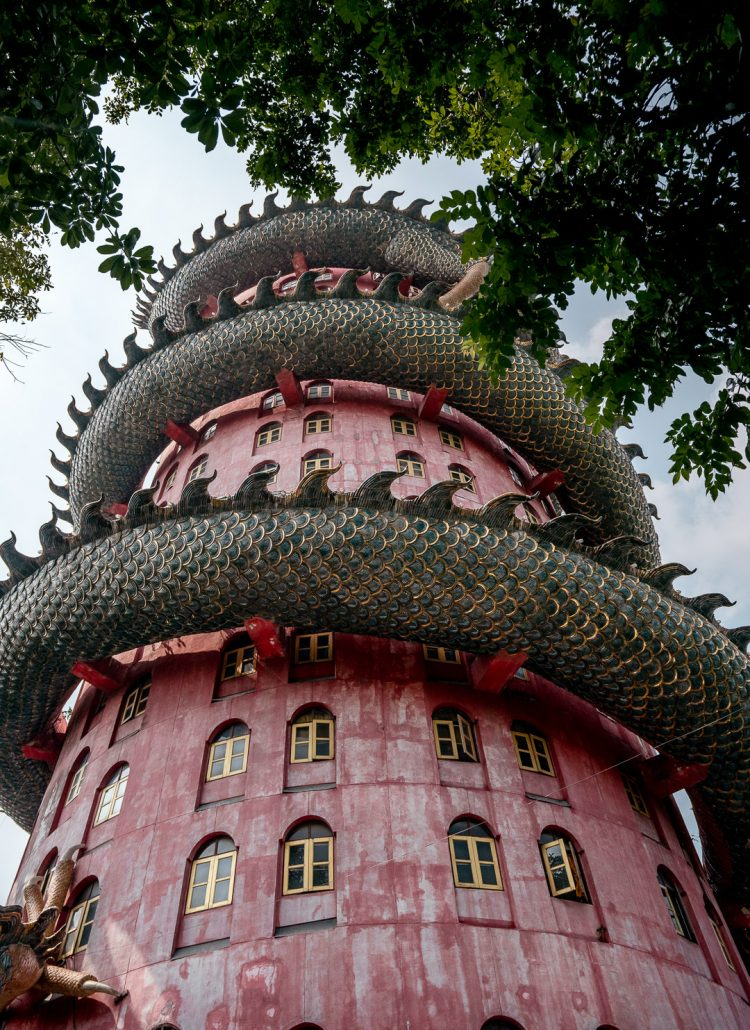 Dragon temple in Bangkok, Thailand is a big cylinder, pink shaped building with a large dragon on top.