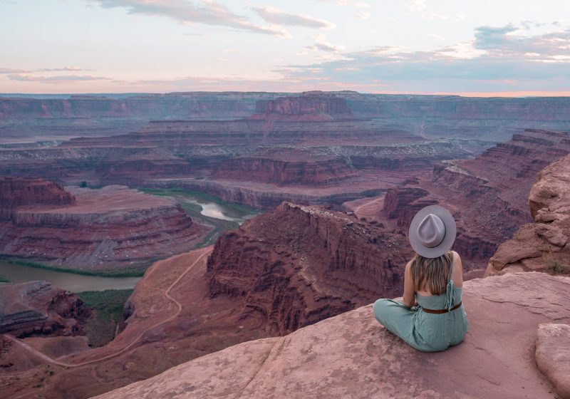 Girl sitting at the edge of Dead Horse Point State Park in Canyonlands, Utah during sunset