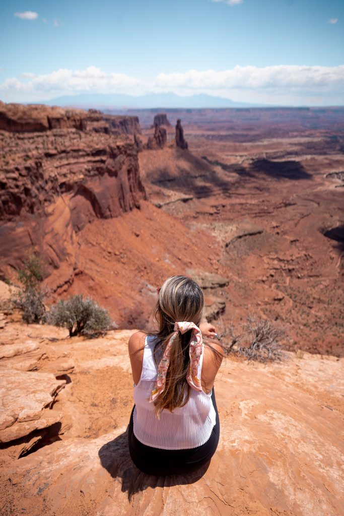 Girl sitting on the edge of an overlook at Mesa Arch in Canyonlands National Park
