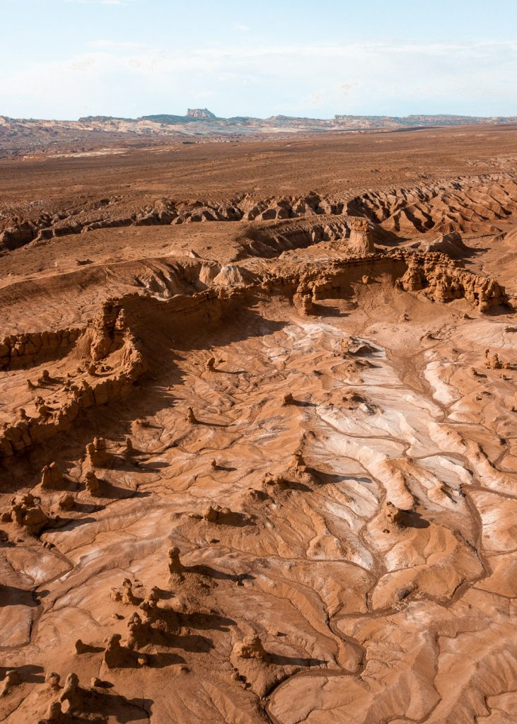 A drone shot of Goblin Valley with lots of hoodoo rock formations in a low lying valley